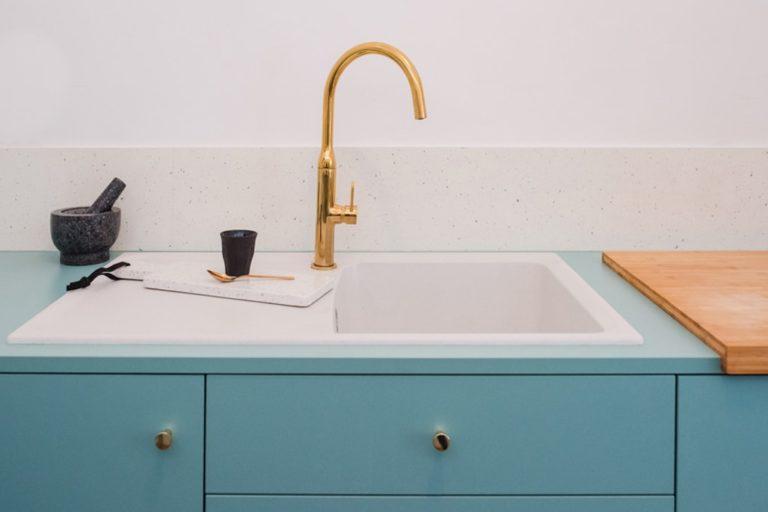 zoom sur l'évier et sa robinetterie dorée d'une cuisine bleu