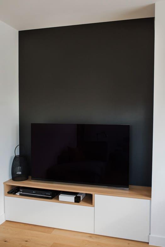 Meuble de TV devant un mur entièrement noir
