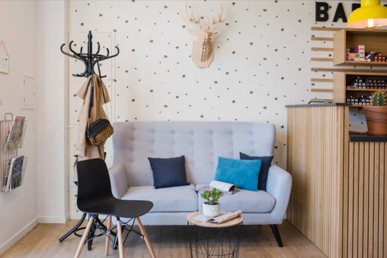 Canapé bleu clair de l'espace attente du salon de coiffure