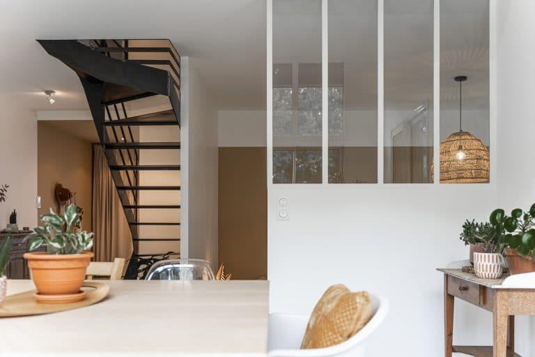 La cuisine blanche contraste avec l'escalier en métal noir