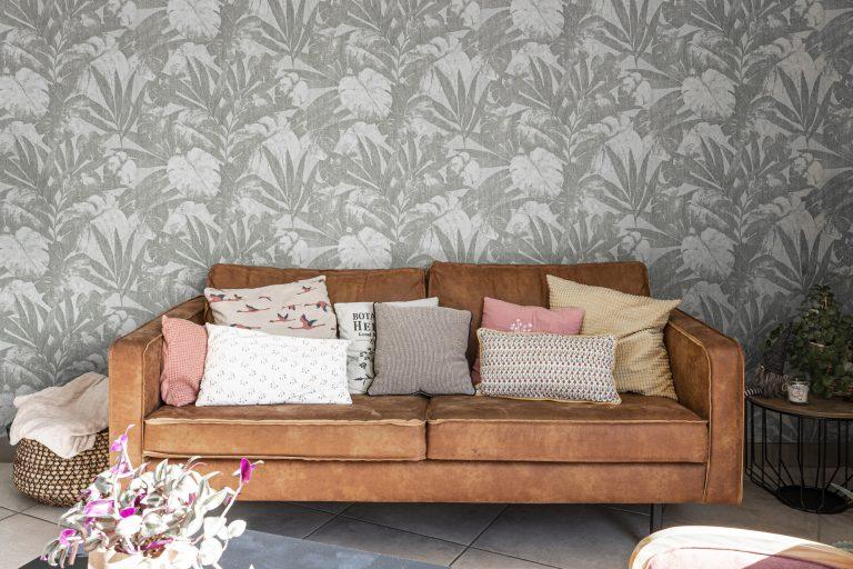 Canapé en cuir marron devant une tapisserie florale