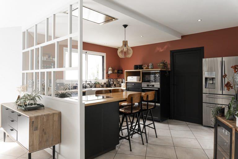 Une verrière blanche originale séparre la cuisine de la pièce de vie